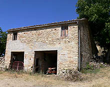 Panoramic stone farmhouse surrounded by a peaceful garden.