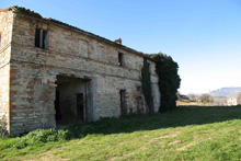 A large farmhouse in need of restoration in the countryside.